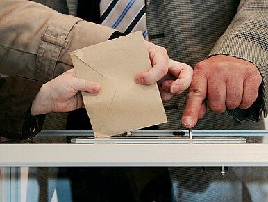 3 hands, 2 together hold a voting ballot and put it into the vote box. The third hand points its finger at the insertion slot